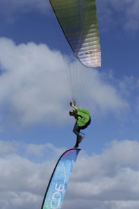 Acro pilot Renan Morales stands on a flag while paragliding